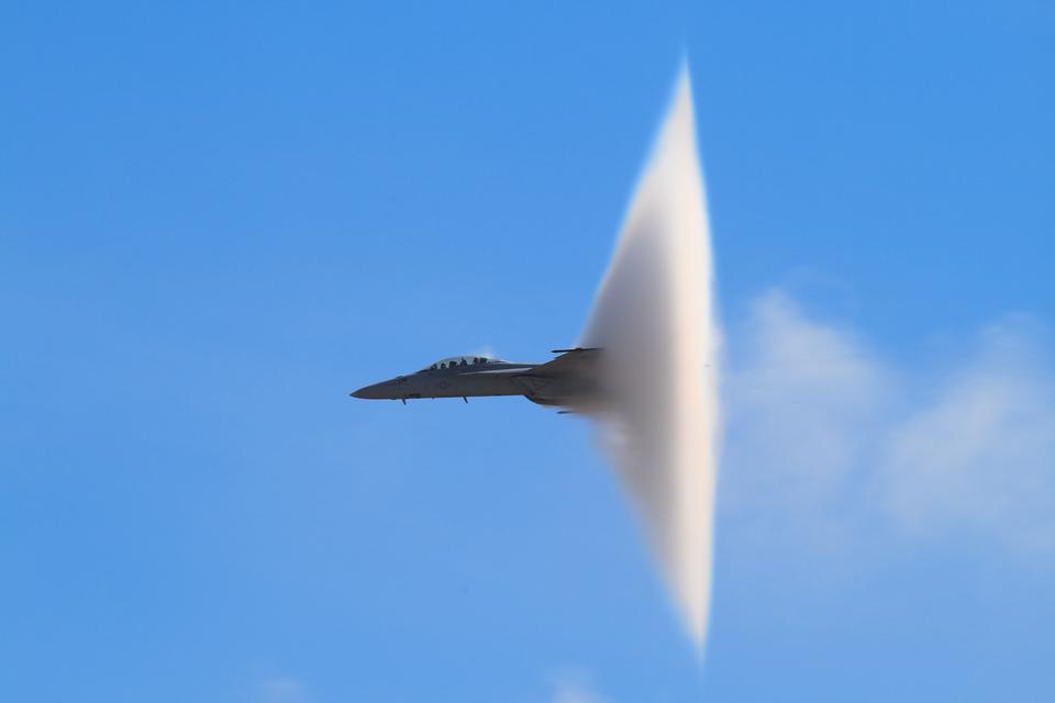 Fotografia przedstawiająca samolot przekraczający prędkość dźwiękową. Zprzodu widoczny kadłub samolotu, ztyłu po przekroczeniu dźwięku widoczna biała chmura