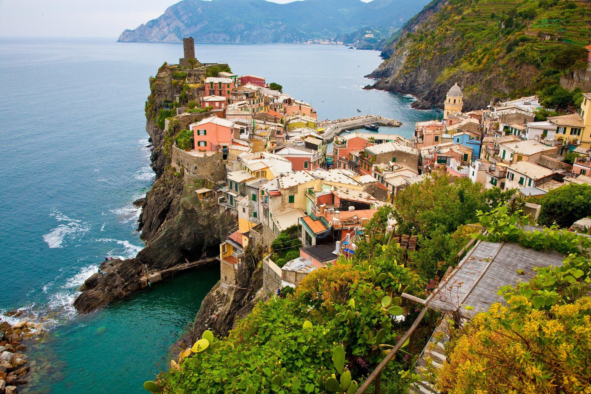 Fotografia prezentuje krajobraz śródziemnomorski na Lazurowym Wybrzeżu. Widoczne skaliste wybrzeże schodzące do lazurowej wody. Na płaskim wysokim cyplu znajdują się gęsto rozmieszczone różnokolorowe budynki.
