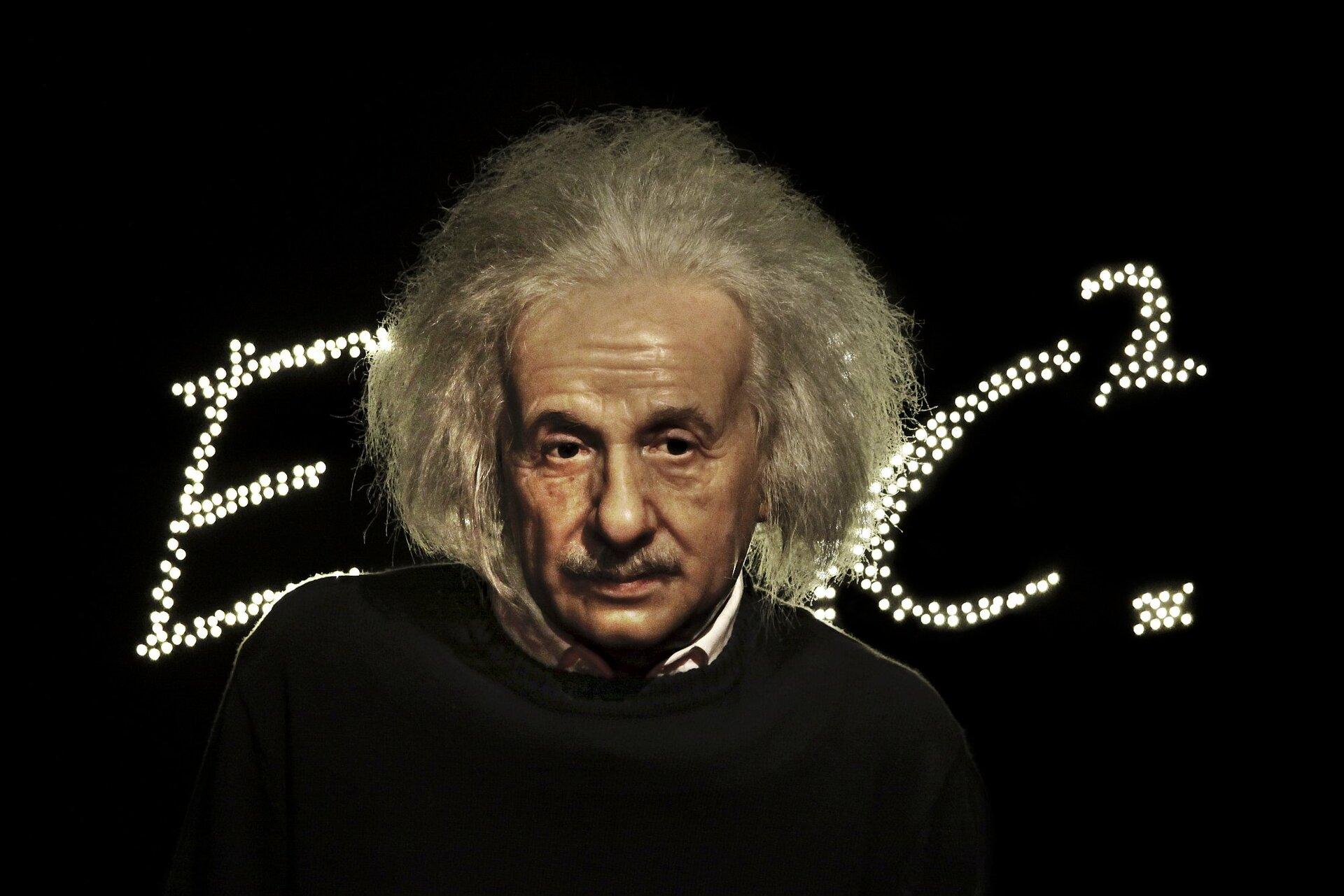 Zdjęcie przedstawia podobiznę Alberta Einsteina, adokładniej mówiąc przedstawiającą go figurę wgabinecie figur naturalnych Madame Tussaud na tle ułożonego zlicznych punktowych świateł wzoru Erówna się mckwadrat. Uczony przedstawiony wwieku średnim ukazany jest od ramion wgórę, spogląda nieco wbok zzamyślonym wyrazem twarzy.