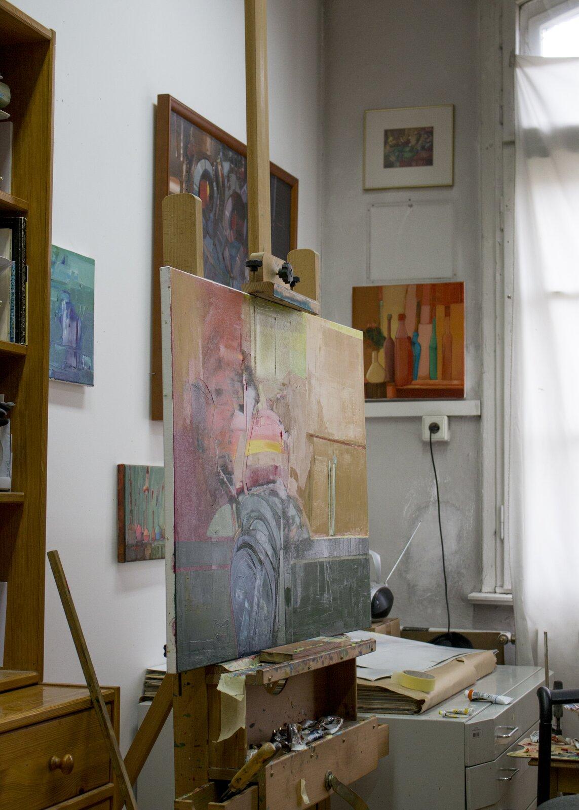 Ilustracja przedstawia fragment wnętrza pracowni malarskiej. Wcentrum kadru znajduje się sztaluga zobrazem olejnym. Za sztalugą ustawiona jest niska, biała szafka zszufladami na której leży duża teczka zrysunkami. Na ścianach pomieszczenia wiszą kolorowe obrazy.