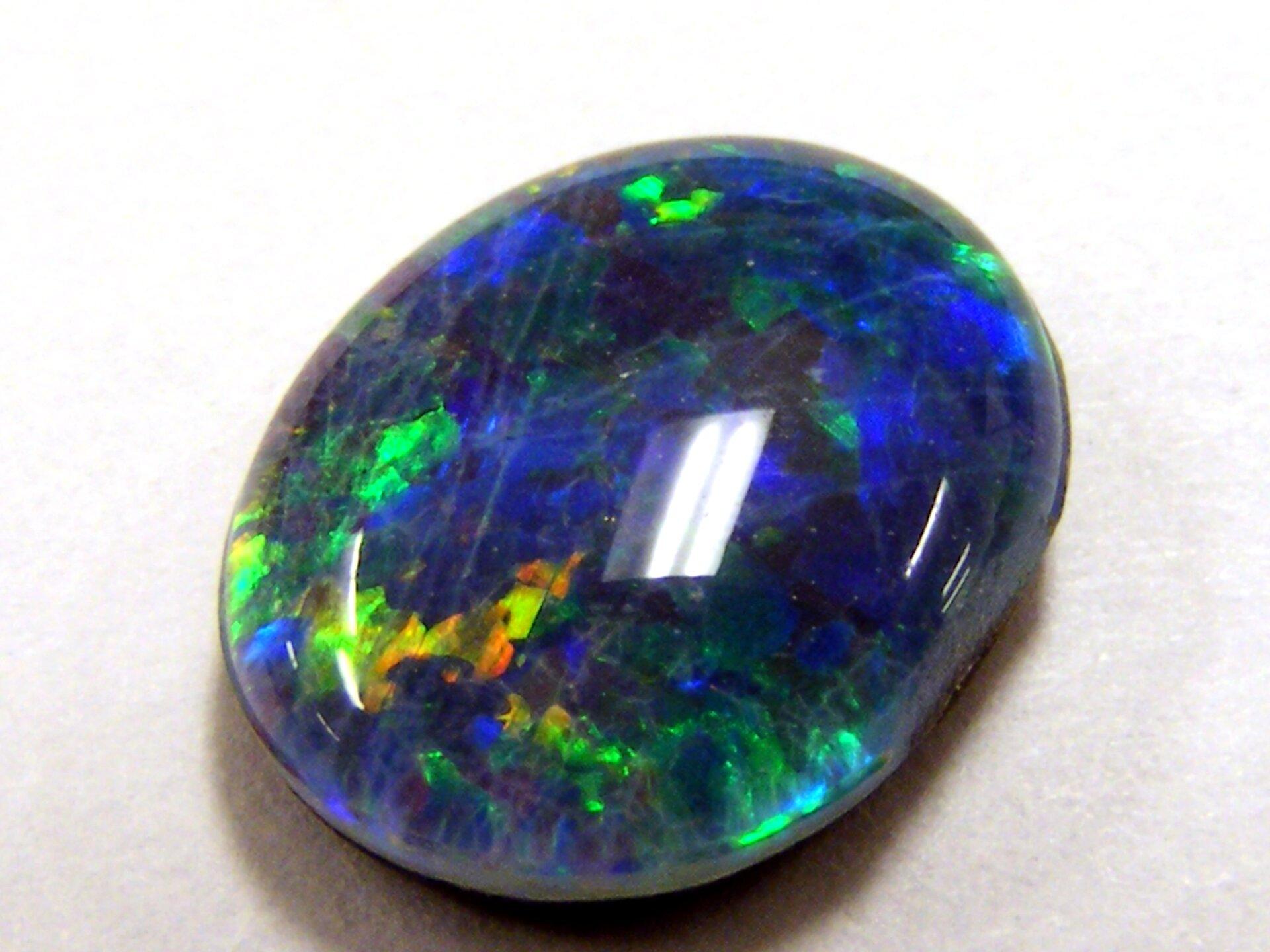 Zdjęcie przedstawia oszlifowany opal niebieski wodmianie szlachetnej, czyli opalizującej, co oznacza zmienność barw wzależności od kąta obserwacji. Szlif owalny, kamień ma formę nieco spłaszczonej kropli.