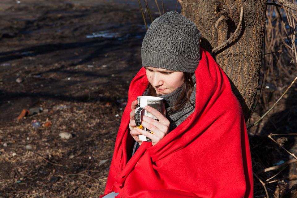 Słoneczny dzień. Kolorowe zdjęcie przedstawia dwunastoletnią dziewczynę siedzącą iopierającą się opień drzewa. Dziewczyna okryta czerwonym kocem. Na głowie szara wełniana czapka. Ubrana wszary pulower zapięty wysoko pod szyją. Wdłoniach trzyma wysoki porcelanowy kubek zherbatą.