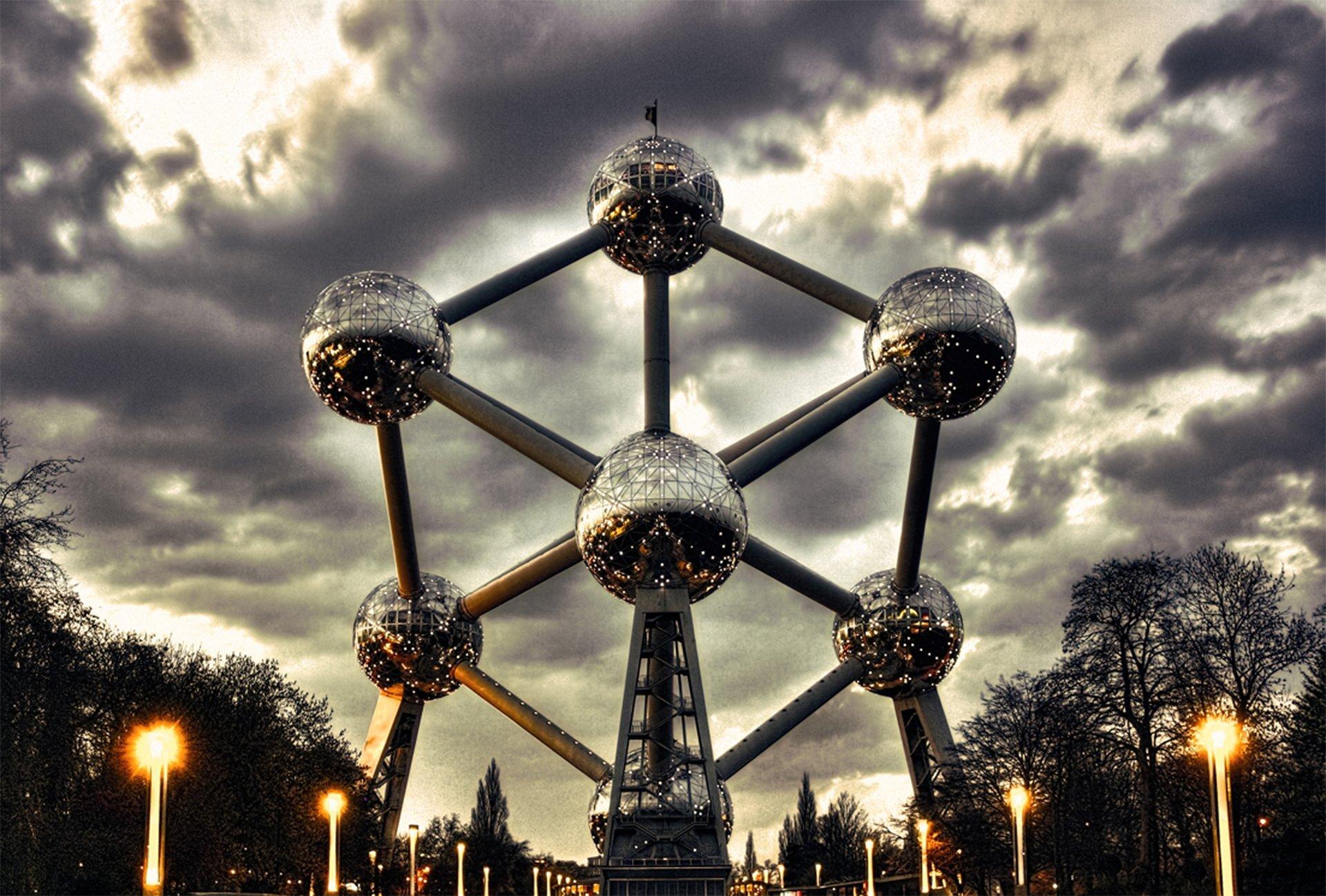 Zdjęcie przedstawia budowlę Atomium składającą się zdziewięciu metalowych kul połączonych ze sobą, zczego na zdjęciu widocznych jest siedem. Zdjęcie wykonano wieczorową porą, przez co od kul odbijają się liczne światła miasta. Na tle Atomium rozpościera się niebo pokryte burzowymi chmurami, poniżej znajdują się drzewa ilatarnie uliczne.