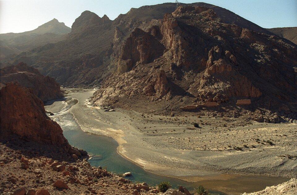 Na zdjęciu głęboka dolina wśród skalistych gór, piaszczyste dno doliny, wsamym jej środku wąską strugą płynie płytka rzeka.