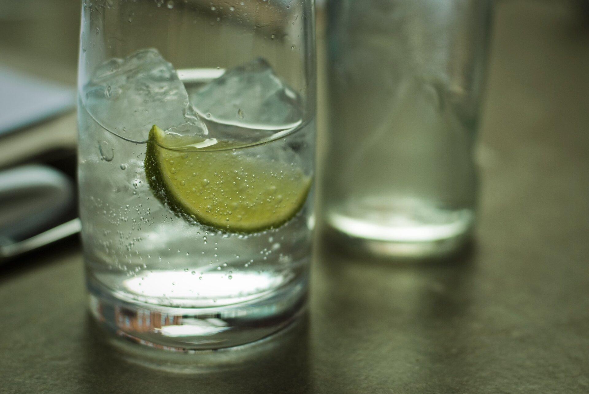 Zdjęcie przedstawia stojącą na stole szklankę do połowy napełnioną wodą mineralną ipływającymi wniej kostkami lodu iplastrem limonki. Wtle zdjęcia wobszarze nieostrości znajdują się pusta szklanka iinne nierozpoznawalne przedmioty.