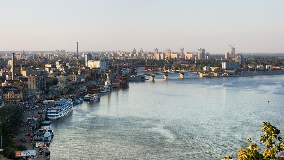 Na zdjęciu szeroka rzeka wdużym mieście. Po lewej stronie widać brzeg rzeki, statki, zwartą zabudowę miejską, mosty.