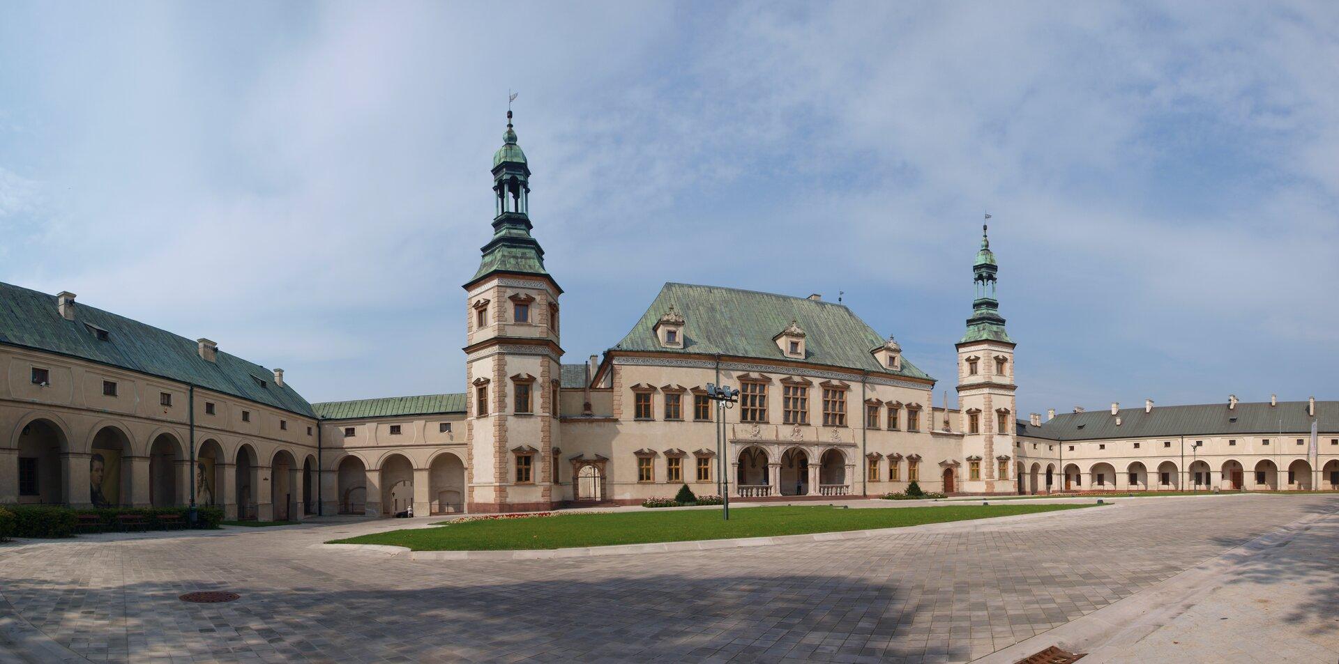 Ilustracja przedstawia pałac biskupów krakowskich wKielcach. Budynek składa się ztrzech części. Głównego budynku ze strzelistymi wieżami, oraz dwóch niższych budynków, które łączą się zgłównym budynkiem. Przed wejściem do pałacu widoczny jest betonowy plac.
