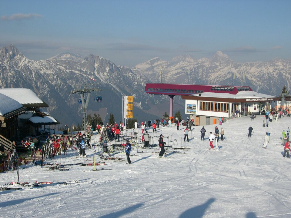 Na zdjęciu górna stacja wyciągu narciarskiego. Zabudowania, ośnieżony stok, narciarze. Wtle wysokie strome góry.