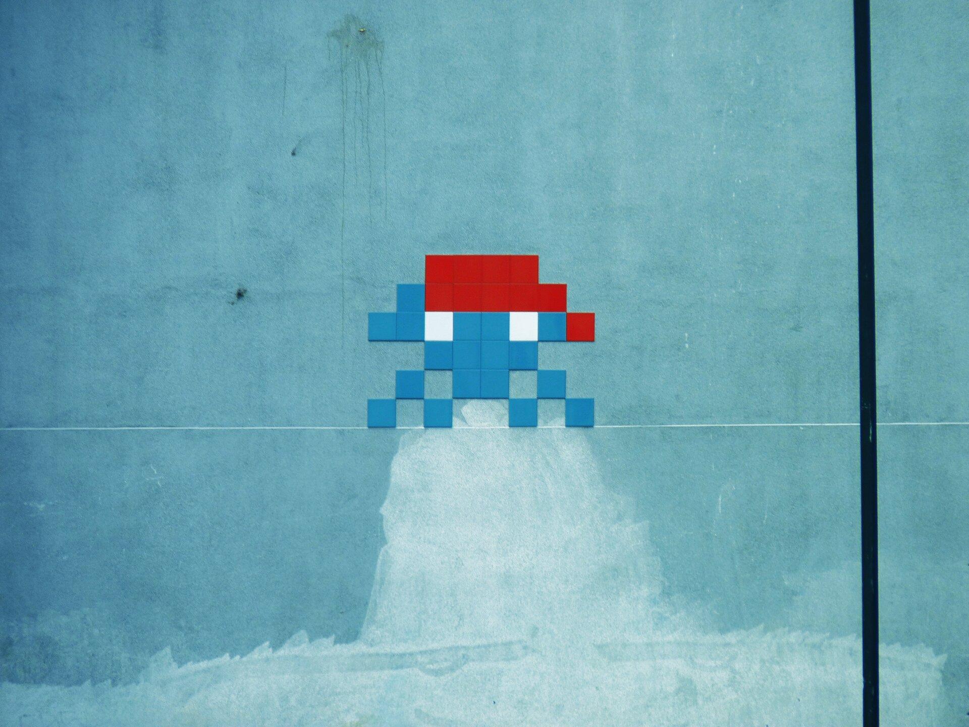 Ilustracja przedstawia unoszący się niebiesko-czerwony obiekt na tle niebieskiej ściany. Składa się zmałych kwadratów iprzypomina swoim wyglądem niewielką rakietę kosmiczną. Obiekt został przez artystę umiejscowiony nad białą plamą na murze, co sprawia wrażenie dymu ulatującego zsilnika rakiety.