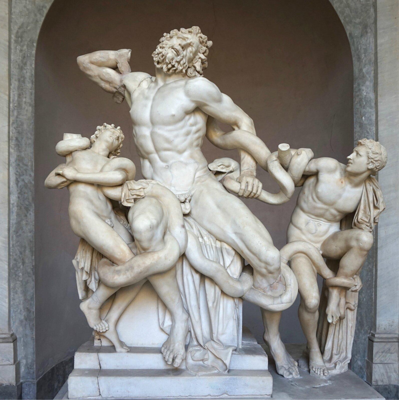 """Ilustracja przedstawia marmurową rzeźbę """"Grupa Laokoona"""" autorstwa Agesandera zRodos. Rzeźba przedstawia siedzącego, nagiego mężczyznę. Po jego obu bokach są postacie nagich młodzieńców, których oplatają węże. Środkowa postać to """"Lakoon"""". Rzeźba ukazuje bardzo realistycznie jego umięśnione ciało. Walczy zwężami trzymając jednego wlewej ręce. Drugą rękę ma podniesioną na wysokości szyi izgiętą włokciu. Prawa ręka jest bez dłoni. Po twarzy widać zmęczenie walką. Postać ma falowane włosy ibrodę. Po lewej stronie stoi młody chłopak zwrócony twarzą wstronę mężczyzny zbrodą. Postać ta stoi na prawej nodze, alewa jest uniesiona do góry. Nie ma prawej dłoni. Postać po prawej stronie mężczyzny to młody chłopak, który wygląda jakby się przewracał do tyłu. Lewą rękę zgina włokciu. Trzyma ją na wysokości klatki piersiowej, adłonią trzyma głowę węża. Nie ma prawej ręki, ajej kikut uniesiony do góry oplata ogon węża."""