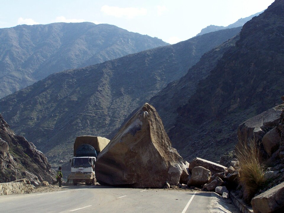 Zdjęcie fragmentu oberwanej skały, który spadł na drogę. Na poboczu stoi ciężarówka. Zprawej strony iwtle wysokie góry.
