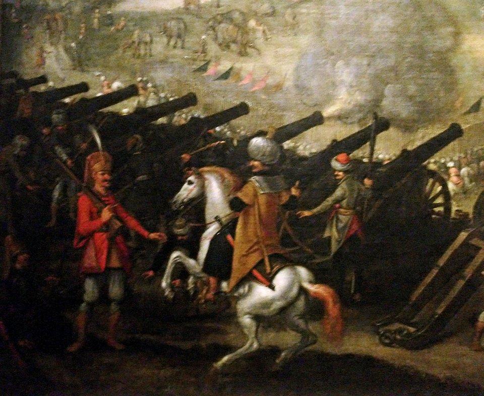 na zdjęciu widać żołnierza (janczara) oraz oficera na koniu. Wtle sa namalowane armaty (widac ich lufy) iniewyraźnepostacie żolnierzy