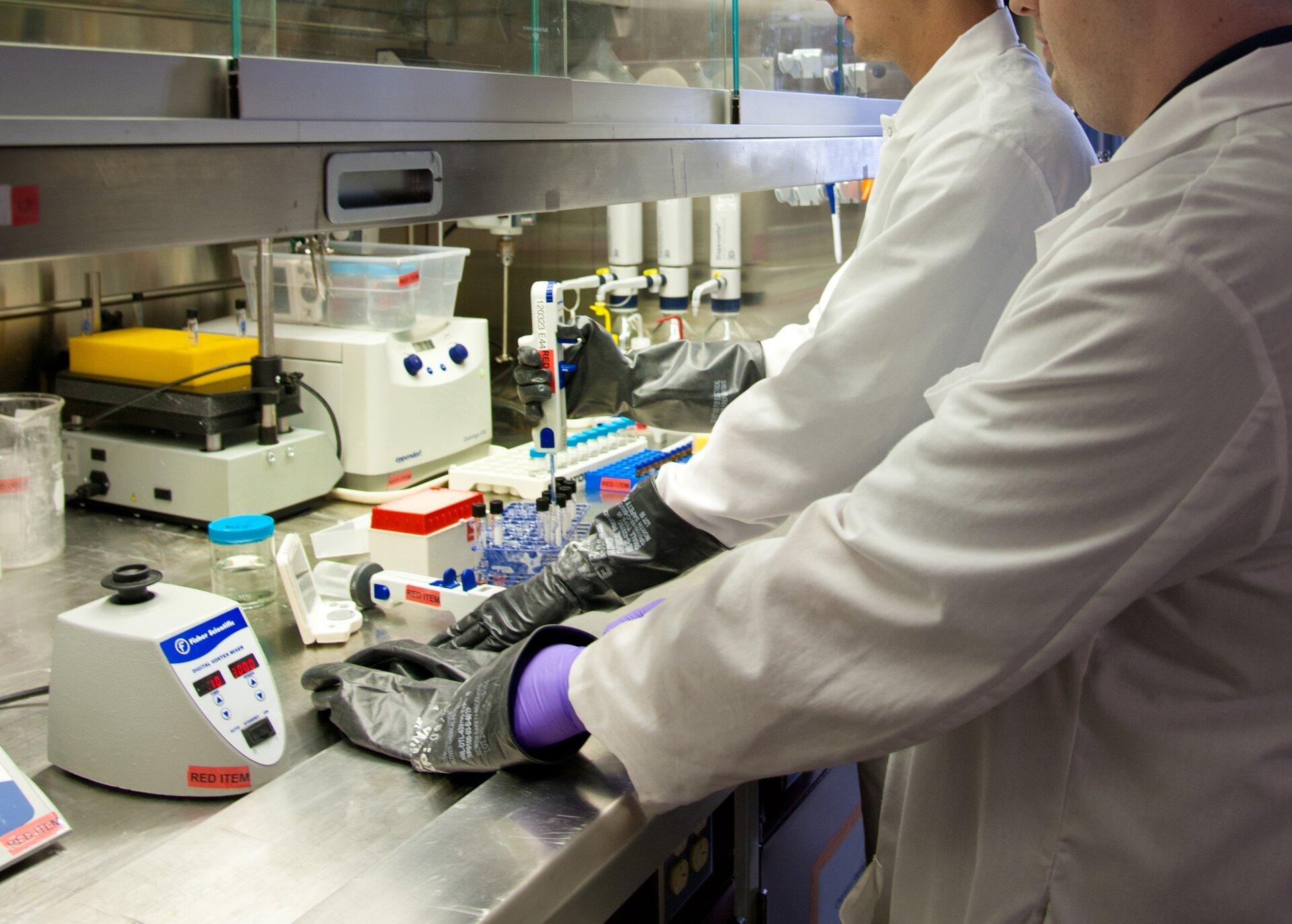 Fotografia przedstawia wnętrze laboratorium. Na metalowym stole znajdują się różne urządzenia iodczynniki. Są tu dwie osoby, ubrane wfartuchy igumowe rękawiczki. Jedna przygotowuje próbki do badania, adruga odczytuje wynik.