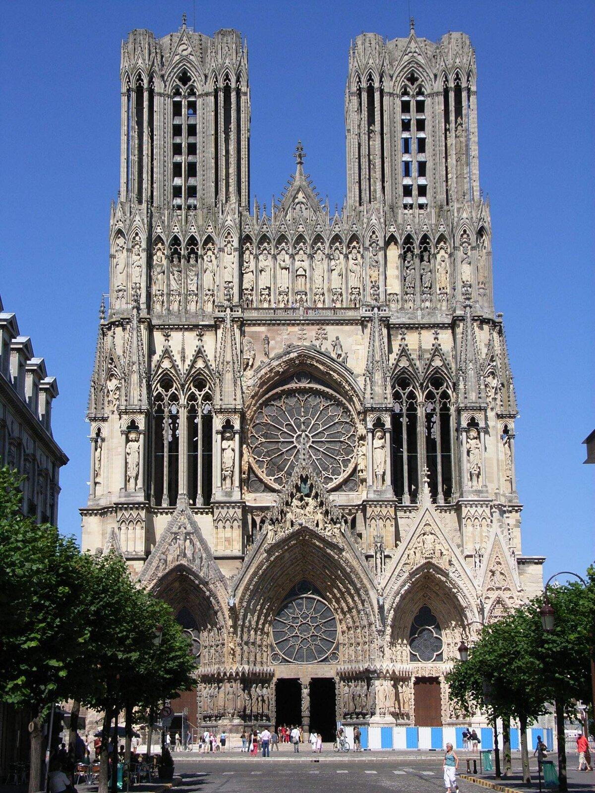 Ilustracja przedstawia budynek gotyckiej katedry wReims we Francji. Budowla pochodzi zXIII wieku. Ukazuje widok od strony zachodniej ztrzema portalami, rozetą nad wejściem głównym oraz bogatą dekoracja wpostaci galerii królów. Katedra posiada dwie wysokie wieże. Fotografia ukazuje bryłę kościoła od strony wejścia, zdrzewami rosnącymi po bokach. Tłem jest niebieskie niebo.