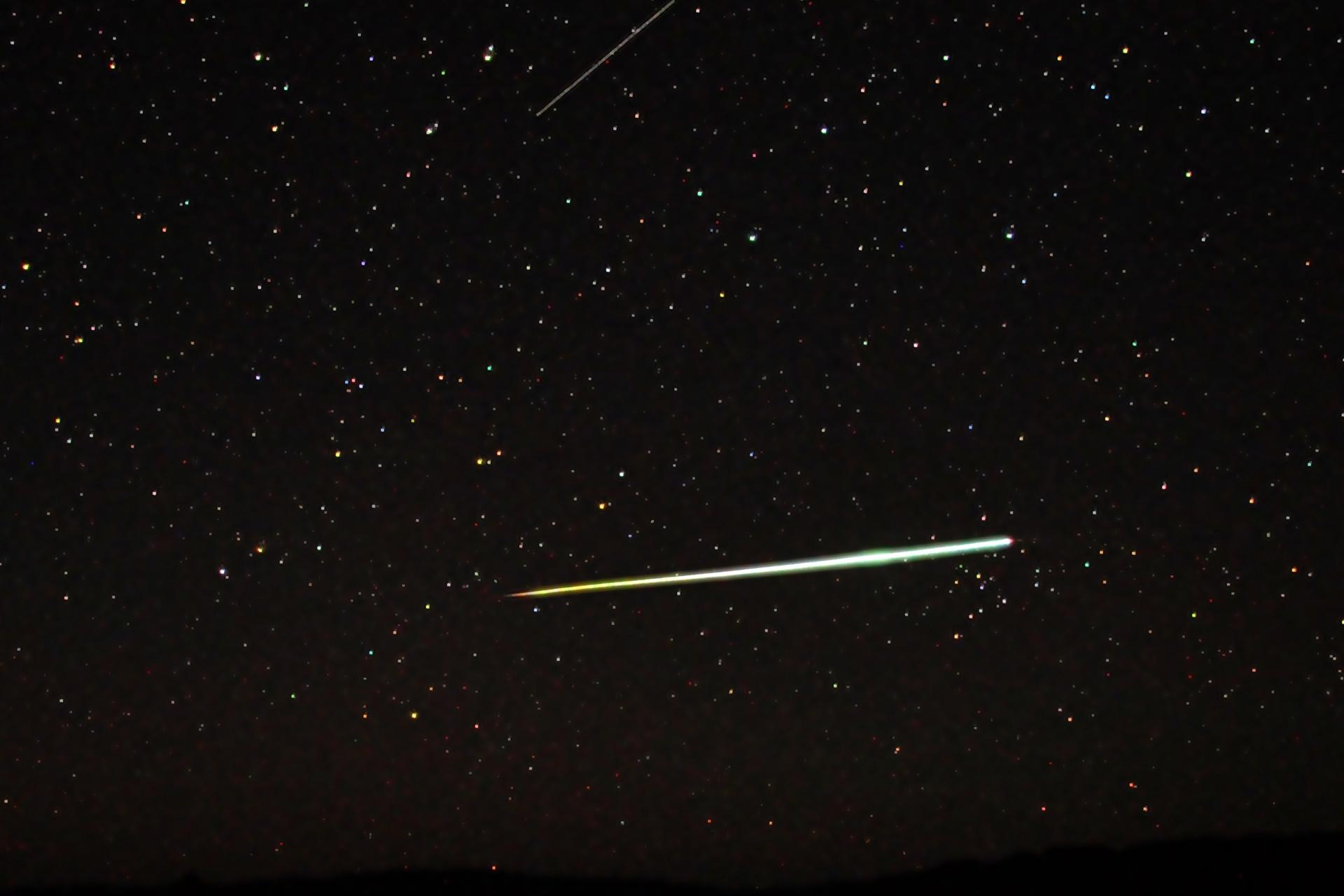 Fotografia prezentuje meteor. Na czarnym niebie widoczne gwiazdy wpostaci białych licznych punkty różnej wielkości. Na środku fotografii widoczna biała wąska smuga.