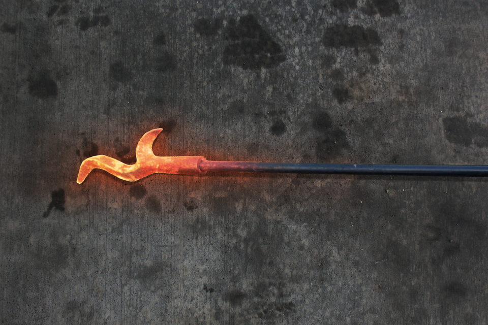 Fotografia przedstawia rozgrzany do czerwoności pręt żelaza – pogrzebacz do pieca lub kominka