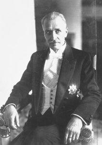 Zdjęcie przedstawia Ignacego Mościckiego zokresu jego prezydentury wlatach 1926 do 1939, siedzącego na krześle zrękami na oparciach bocznych ispoglądającego wprzestrzeń po prawej stronie fotografa.