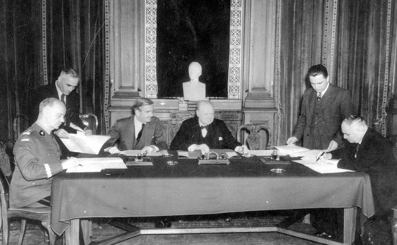 Przy stole nakrytym suknem, stojącym przed kominkiem na którym stoi popiersie mężczyzny siedzą na jednym szczycie generał Sikorski wmundurze, naprzeciwko niego siedzi ambasador Majski. Generał Sikorski iambasador Majski podpisują dokumenty. Obok generała iambasadora stoją ich asystenci. Po środku, przy dłuższym boku stołu siedzi Winston Churchill aobok niego siedzi jego asystent. Na stole leżą dokumenty ipojemniki zatramentem.