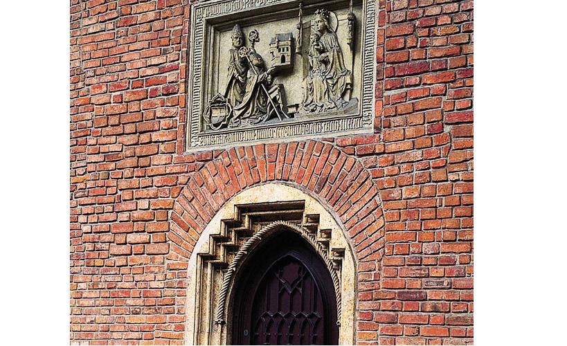 Fotografia przedstawiająca tablicę erekcyjną Akademii Krakowskiej. Tablica umieszczona jest nad frontowym wejściem do zbudowanego zczerwonej cegły budynku. Przedstawia jej fundatora — Kazimierza III Wielkiego siedzącego na tronie królewskim iprzyjmującego dary.