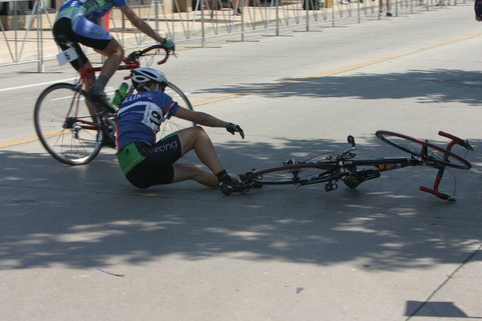 Zdjęcie przedstawia wypadek zudziałem rowerzysty, do jakiego doszło podczas wyścigów kolarskich. Słoneczny dzień. Na pierwszym planie asfaltowa ulica, na środku której widoczny jest cień drzewa. Wcieniu przewrócony rowerzysta ileżący rower po prawej stronie kadru. Rowerzysta ubrany jest wkrótkie spodnie do kolan oraz niebieską koszulkę zkrótkim rękawem, ana głowie ma kask. Na plecach numer zawodnika biorącego udział wwyścigu rowerowym. Rowerzysta siedzi na asfalcie ipróbuje wstać. Wtle drugi rowerzysta jedzie na rowerze mijając przewróconego zlewej strony. Wtle zdjęcie barierki ustawione wzdłuż ulicy.