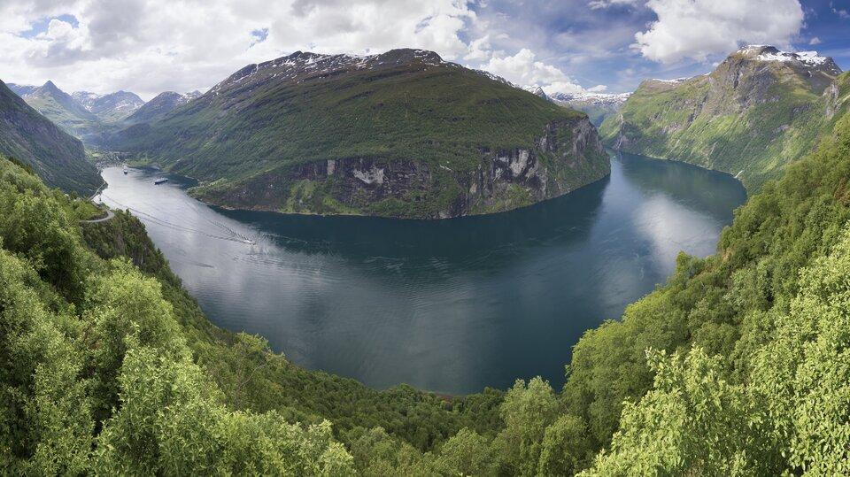 Na zdjęciu fjord otoczony wysokimi stromymi skalistymi zboczami. Część stoków na pierwszym planie porośnięta lasami liściastymi.