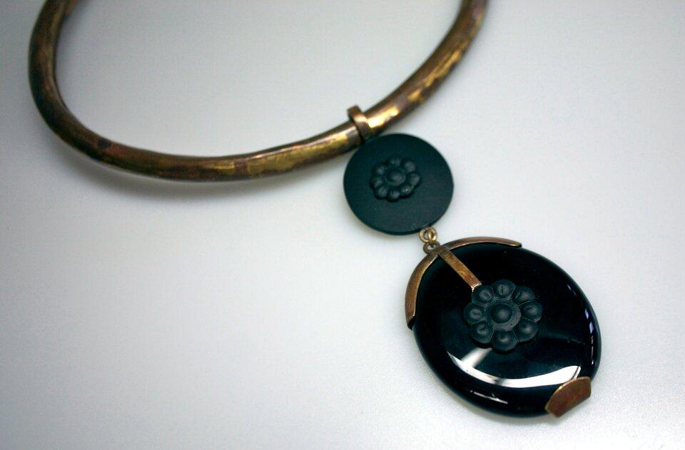 Zdjęcie przedstawia stary metalowy naszyjnik, wktóry wprawiono czarny, gładko oszlifowany onyks oowalnym kształcie.