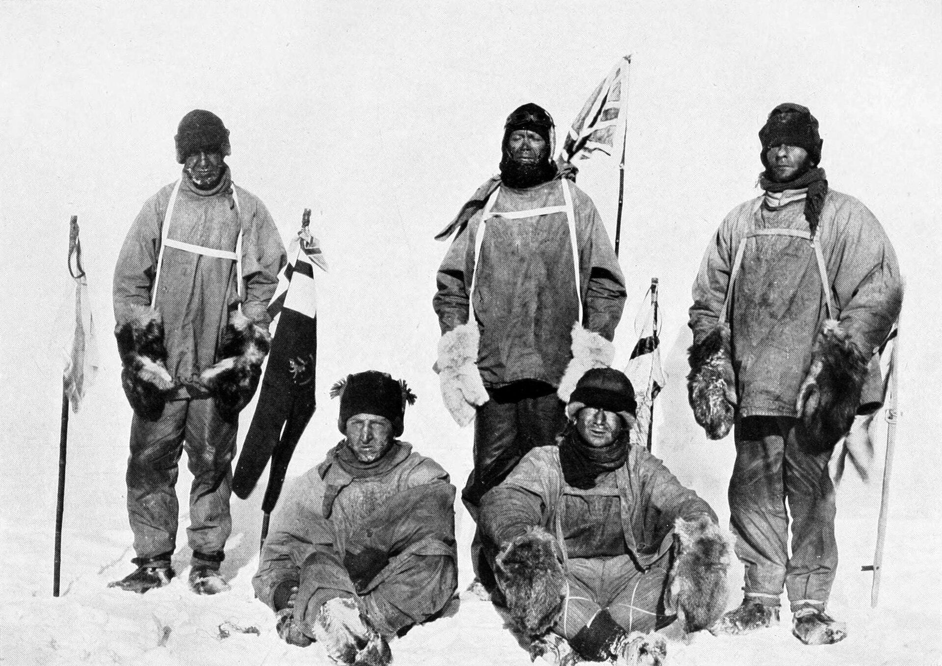 Na zdjęciu pięciu mężczyzn wciepłych strojach ifutrzanych rękawicach. Za nimi wbita wśnieg flaga brytyjska.