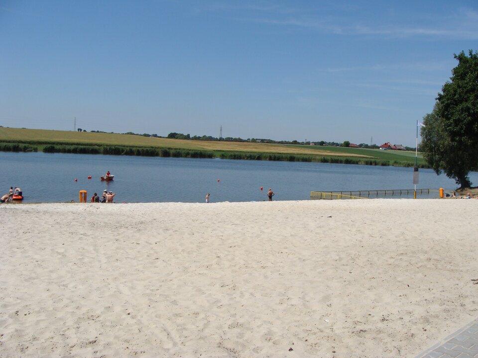 Na zdjęciu zbiornik wodny, piaszczysta plaża. Wtle rozległa równina, zabudowania.