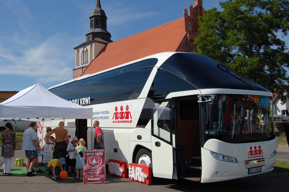 Akcja zbierania krwi. Na zdjęciu widać specjalnie wyposażony do pobierania krwi autobus-ambulans znamiotem do rejestracji. Pod namiotem stoją dorośli zapisując się do oddania krwi. Obok dzieci bawią się balonem. Autobus stoi pod kościołem na ulicy.
