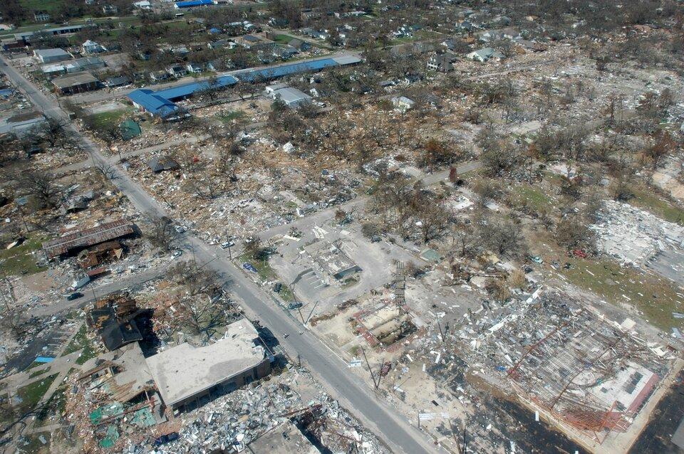 Zdjęcie przedstawia miejscowość po przejściu huraganu oglądaną ze wzgórza lub nisko lecącego helikoptera. Słoneczny dzień. Na pierwszym planie gruz iresztki zniszczonych domów. Przez środek zdjęcia, zprawego dołu, wlewo, wgórę, biegnie asfaltowa droga. Droga jest przejezdna. Po obu stronach drogi ruiny domów. Wtle zdjęcia, wgórnym lewym rogu, budynki mieszkalne pokryte jasnoniebieskim dachem. Wokół zniszczonych budynków drzewa bez liści. Da się wyróżnić dość wyraźne rozgraniczenie obszarów ze zniszczeniami całkowitymi na planach pierwszym iśrednim oraz znikomymi wtle, co sugeruje, że ognisko huraganu miało bardzo wyraźne granice.