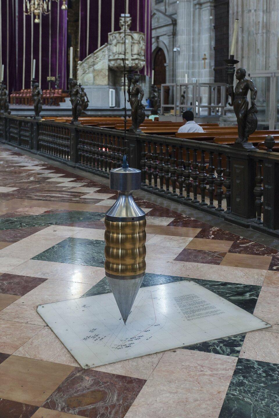 Zdjęcie przedstawia podłużne wahadło wkształcie przypominającym pocisk karabinowy skierowany czubkiem wdół wiszące tuż nad podłogą katedry. Katedra bogato wyposażona, wtle m.in. marmurowa ambona ipurpurowe draperie, posadzka zróżnobarwnych płyt marmurowych. Wahadło wisi na długiej lince zawieszonej pod odległym stropem. Pod wahadłem zamontowana miała płyta znaniesioną siatką geometryczną, ścieżkami ruchu, wyliczeniami iopisami.