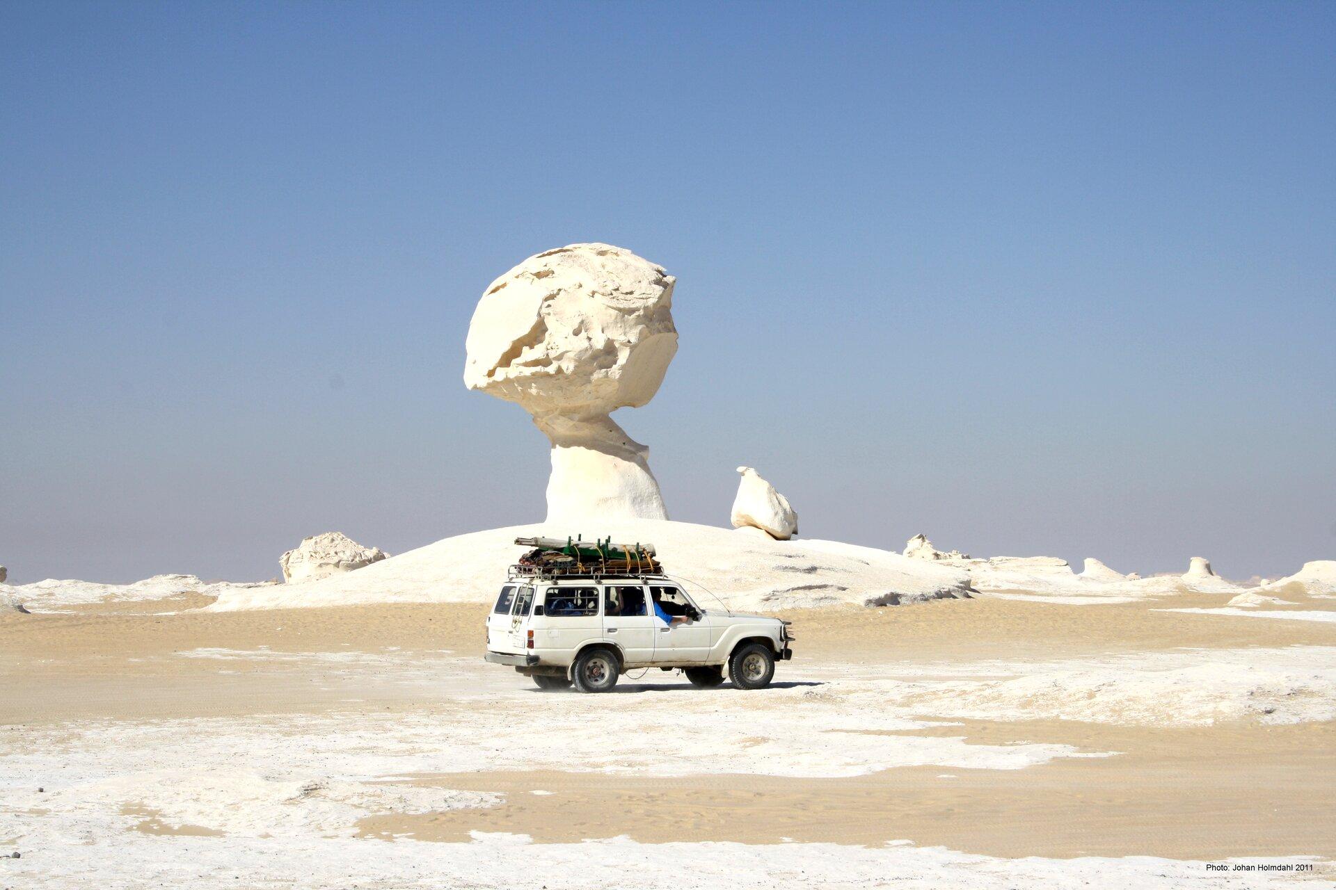 Na zdjęciu grzyb skalny na pustyni. Podstawa ma kształt walca, na jego czubku jest kula. Bardzo jasny kolor piasku. Na pierwszym planie płaski teren pustynny. Biały samochód terenowy, trzy razy mniejszy od grzyba.