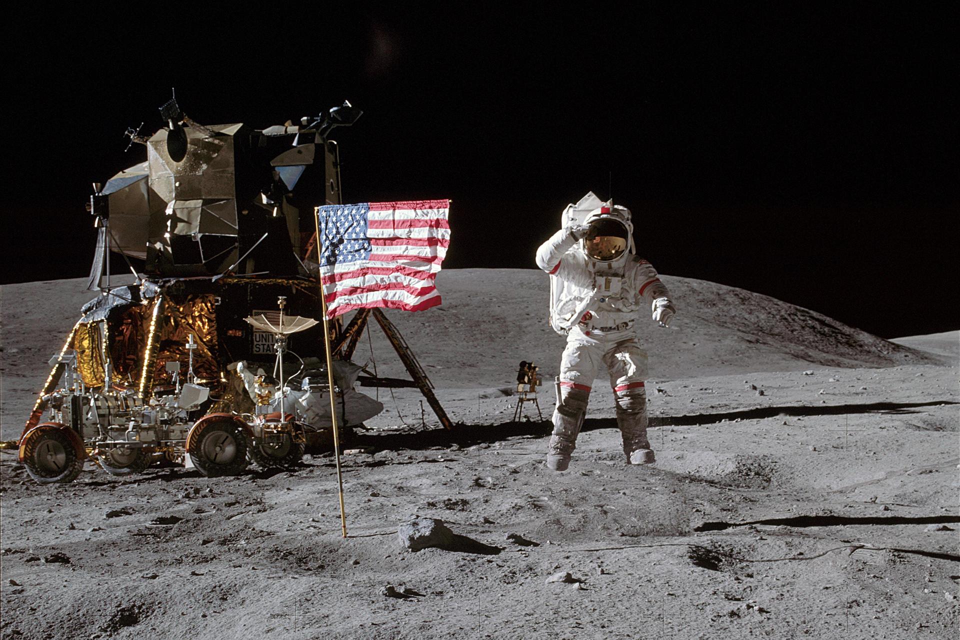 Fotografia prezentuje pierwszego człowieka na księżycu. Na pierwszym planie widoczny kosmonauta wbiałym kombinezonie stojący na powierzchni księżyca, po jego prawej stronie powiewa flaga amerykańska. Na lewo od kosmonauty widoczny pojazd, wtle czarne niebo.