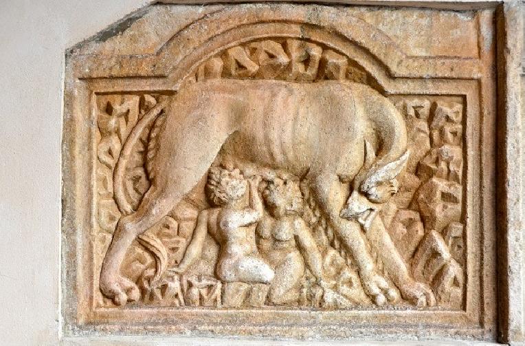 Płaskorzeźba zkremowego piaskowca, przedstawiająca wilczycę karmiącą Romulusa iRemusa. Wilczyca stoi. Głowę ma zwróconą wstronę dzieci, które siedząc pod jej brzuchem wyciągają ręce igłowy do wymion. Tło płaskorzeźby zdobione jest wytłoczeniami. Całość jest fragmentem zdobiącym jakąś większą budowlę.