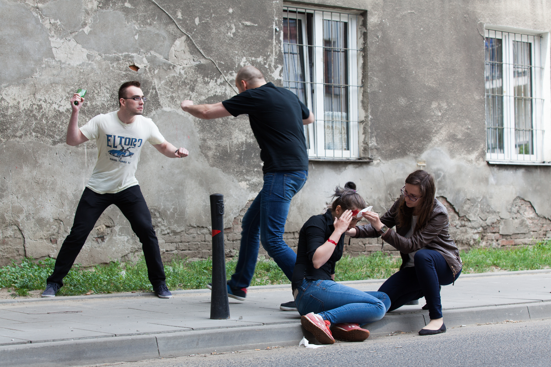 Zdjęcie pokazujące osobę poszkodowaną zkrwawiącą głową siedzącą na krawędzi chodnika. Wtle odrapana fasada budynku. Świadek udziela pierwszej pomocy atuż przy nim widać dwie osoby, które się biją. Jedna znich trzyma rozbitą butelkę.