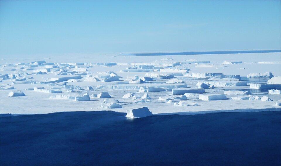 Fotografia wodcieniach bieli ibłękitu przedstawia krajobraz lodowej pustyni na Antarktydzie. Na pierwszym planie płaszczyzna wody. Gdzieniegdzie leżą fragmenty lodu.