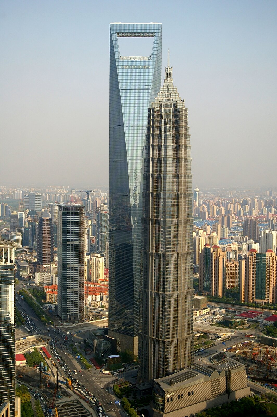 Zdjęcie przedstawia Światowe Centrum Finansowe wSzanghaju, niemal 500 metrową szklaną wieżę zwieńczoną otworem wkształcie trapezu oszerokości 50 metrów. Tuż przed nim silnie kontrastujący nieco niższy wieżowiec Jin Mao Tower zelewacją łączącą szkło istal, przez co na tle niebieskiego szklanego wieżowca wydaje się brązowy.