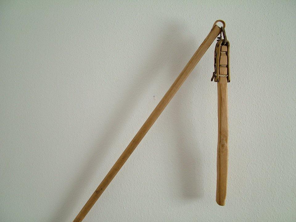 Na końcu długiej tyczki sznurkiem irzemieniem przyczepiony jest krótszy drąg.
