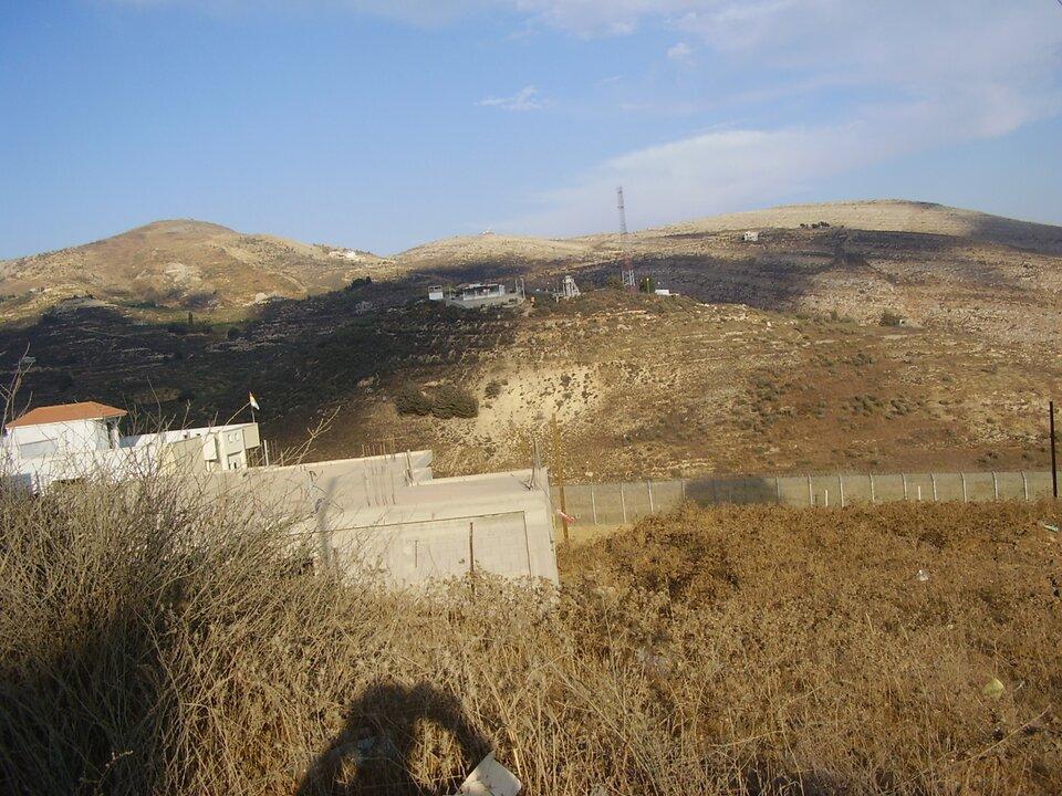 Na zdjęciu łagodne wzgórza wterenie pokrytym suchą roślinnością. Pośrodku niewielkie zabudowania.