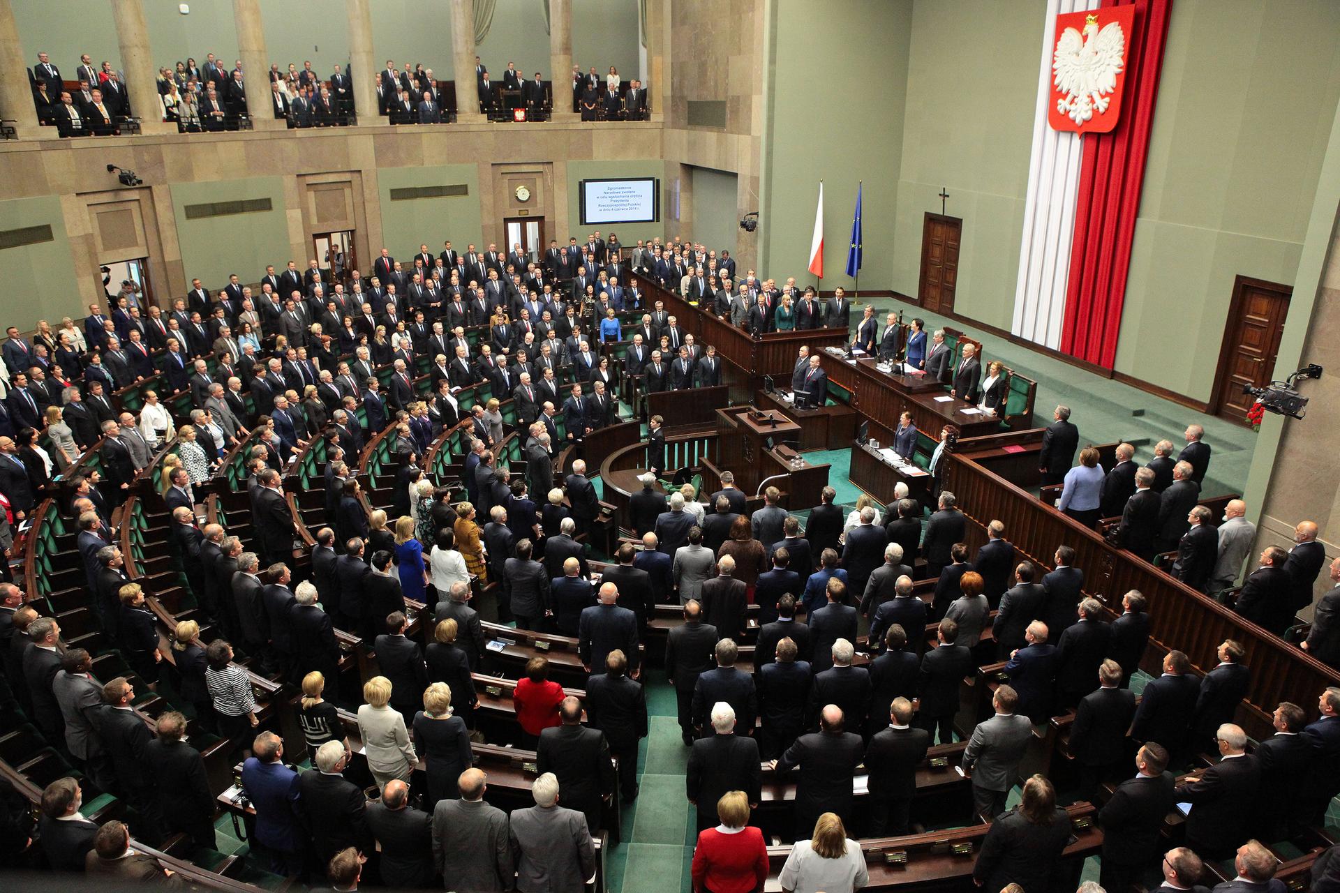 Kolorowe zdjęcie przedstawia salę Sejmu RP. Zdjęcie zgóry. Sala wkształcie półokręgu. Po prawej stronie wysoka ściana. Na środku, wpionie, zawieszony materiały zzakładkami. Po lewej stronie kolor biały, po prawej kolor czerwony. Na materiale zawieszone duże godło Polski. Biały orzeł wkoronie na czerwonym tle. Przed ścianą zgodłem długi rząd ławek równolegle do ściany. Pozostała część sali wkształcie półokręgu. Siedzenia ułożone wformie ławek, wkształcie półokręgów. Osoby biorące udział wposiedzeniu stoją przed swoimi krzesłami. Wcentralnej części sali, wśrodku półokręgu, mównica. Wokół sali balkon wsparty na kolumnach. Na balkonie obserwatorzy posiedzenia Sejmu.