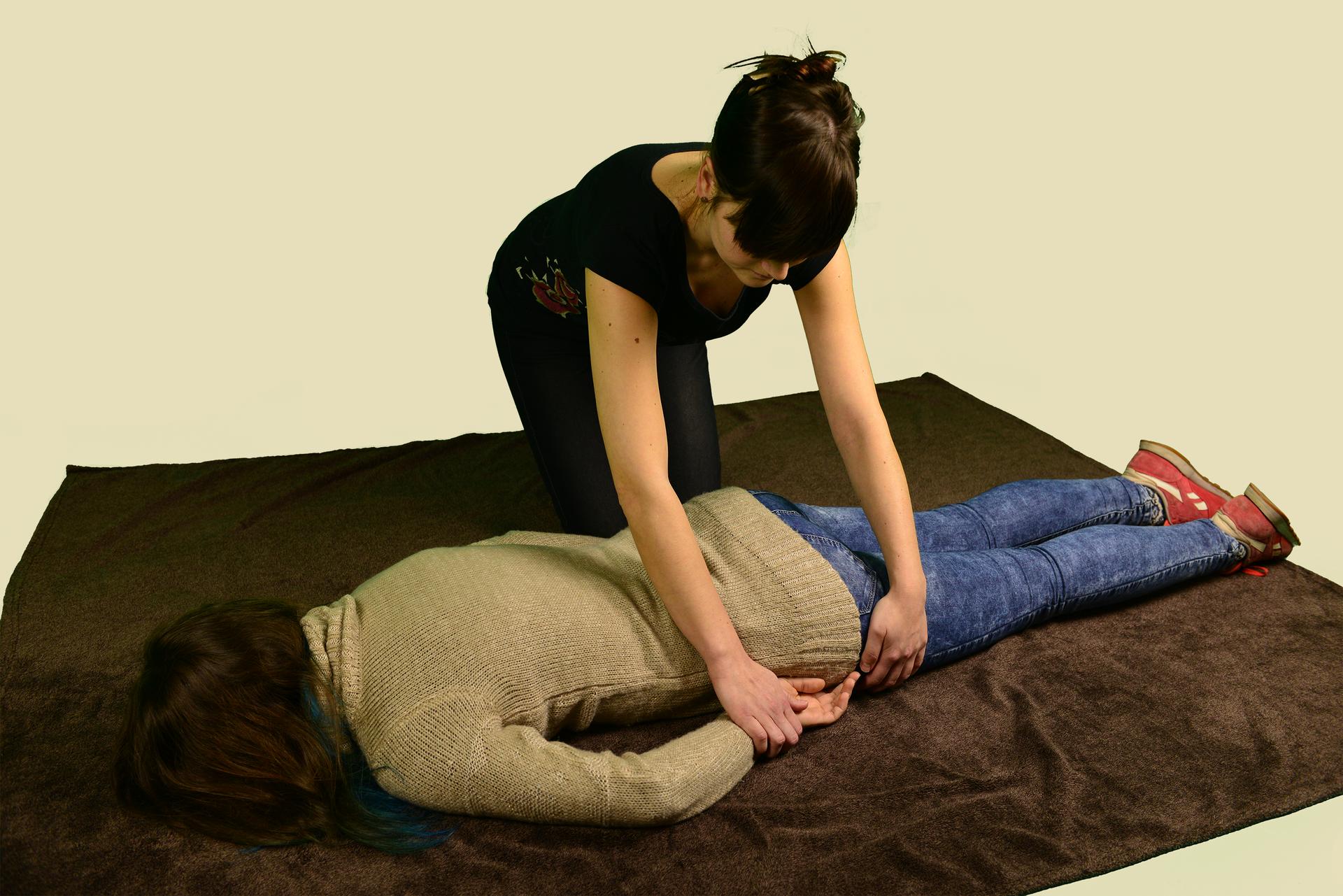 Poszkodowana osoba leży na brzuchu. Ręce ułożone wzdłuż tułowia. Nogi proste, równolegle do siebie. Twarz zwrócona do podłoża. Osoba leży zwrócona głową wlewą stronę zdjęcia. Obok poszkodowanej osoby, wgłębi zdjęcia, klęczy kobieta układająca poszkodowaną osobę wpozycji bezpiecznej. Kobieta przytrzymuje dłoń ibiodro osoby leżącej. Dłoń wkłada pod biodro.