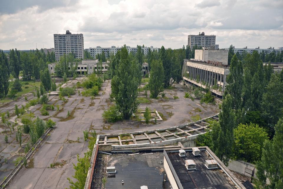 Fotografia prezentuje opuszczone miast Prypeć. Fotografia wykonana zwysokości. Widoczne liczne budynki oraz duży zaniedbany betonowy plac, na którym gdzieniegdzie rosną drzewa ikrzewy.