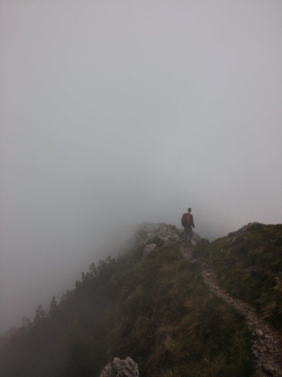 na zdjęciu widać mężczyznę idącego szlakiem wgórach, przed nim jednak gęsta mgła