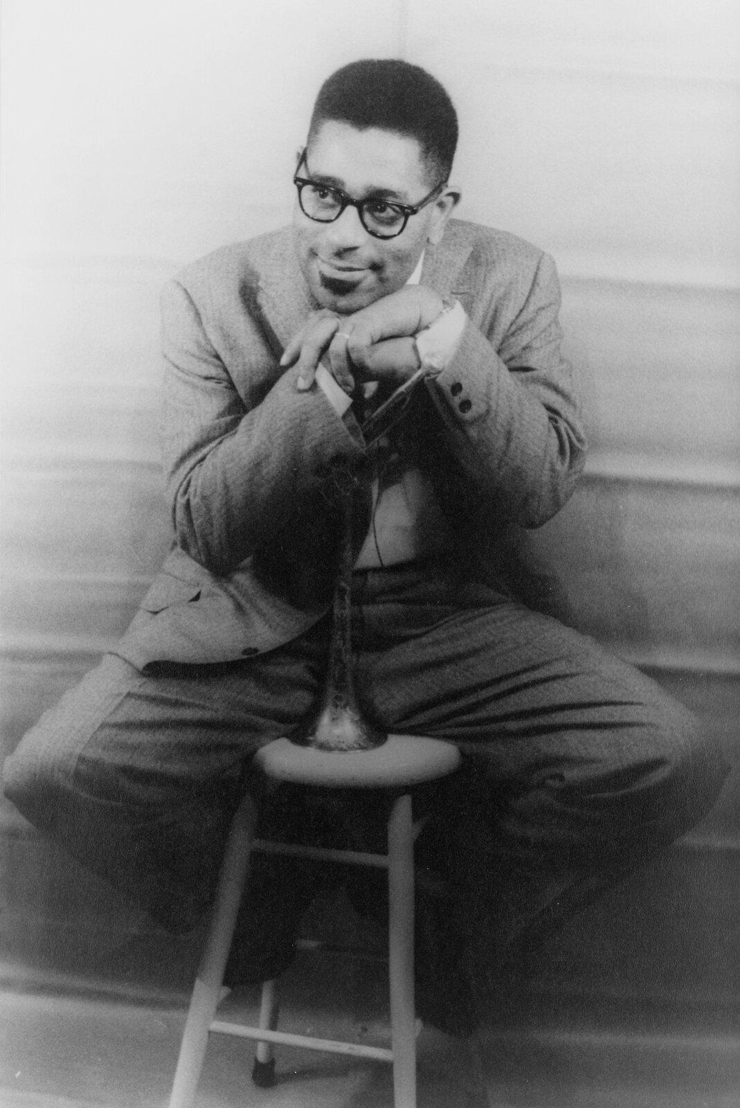 Ilustracja przedstawia zdjęcie słynnego amerykańskiego muzyka Dizziego Gillespie. Mężczyzna siedzi na taborecie, brodę podpiera otrąbkę, która trzyma wręce. Mężczyzna nosił okulary, ubrany wbiałą koszulę ijasny garnitur.