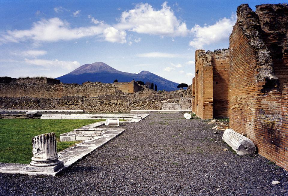 Na zdjęciu ruiny, kolumny, fragmenty murów. Wtle stożek wulkaniczny.