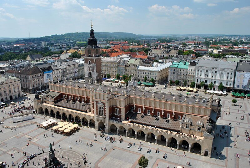 Na fotografii widać dwa budynki stojące na środku krakowskiego rynku – Sukiennice iwystającą zza nich wieżę ratusza Na fotografii widać dwa budynki stojące na środku krakowskiego rynku – Sukiennice iwystającą zza nich wieżę ratusza Źródło: Maatex, Wikimedia Commons, licencja: CC BY-SA 3.0.