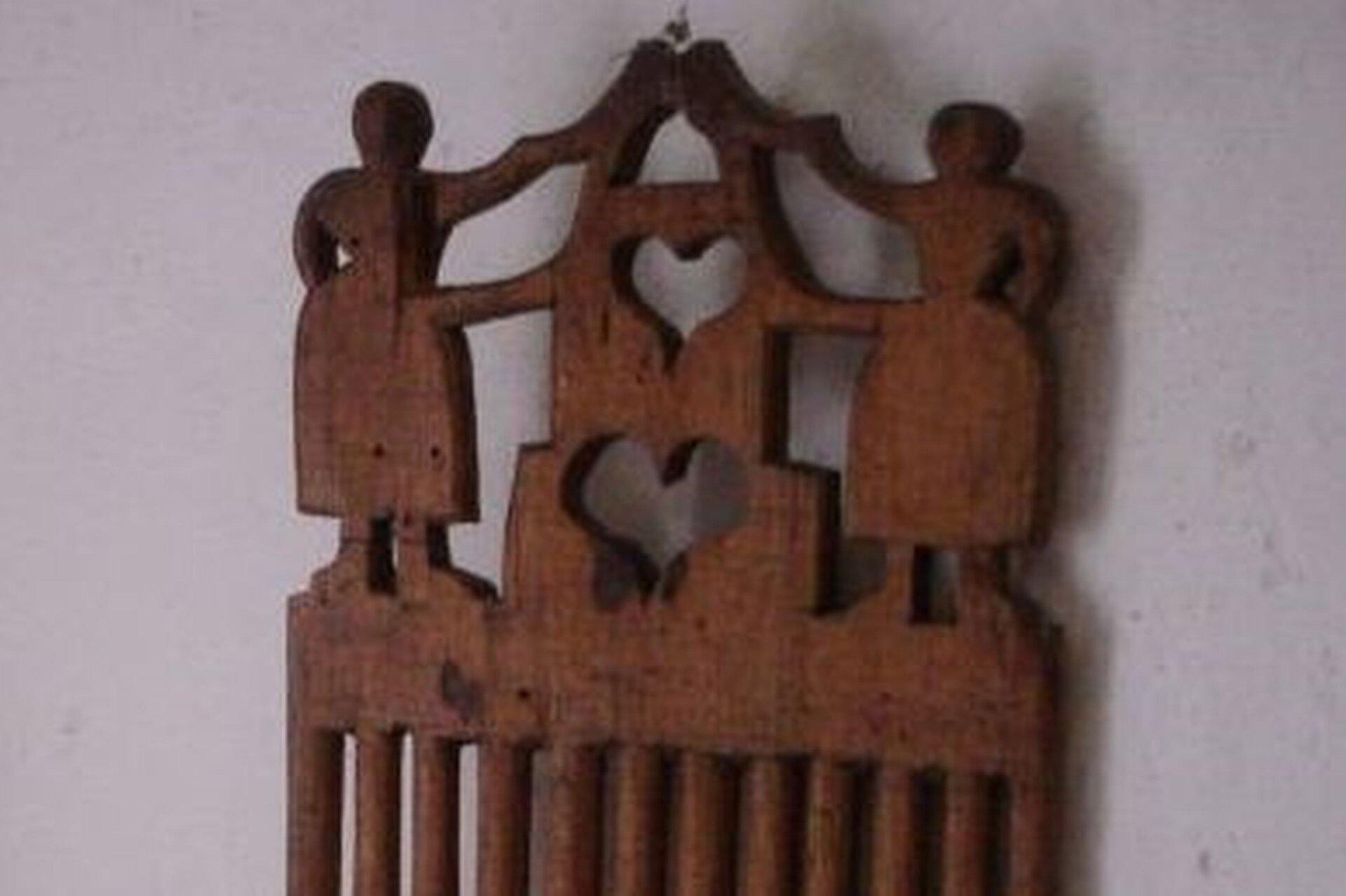 Ilustracja przedstawia zdobioną drewnianym ornamentem deskę do tkania. Rzeźby to postacie dwóch kobiet między którymi są dwa serca umieszczone jedno pod drugim.