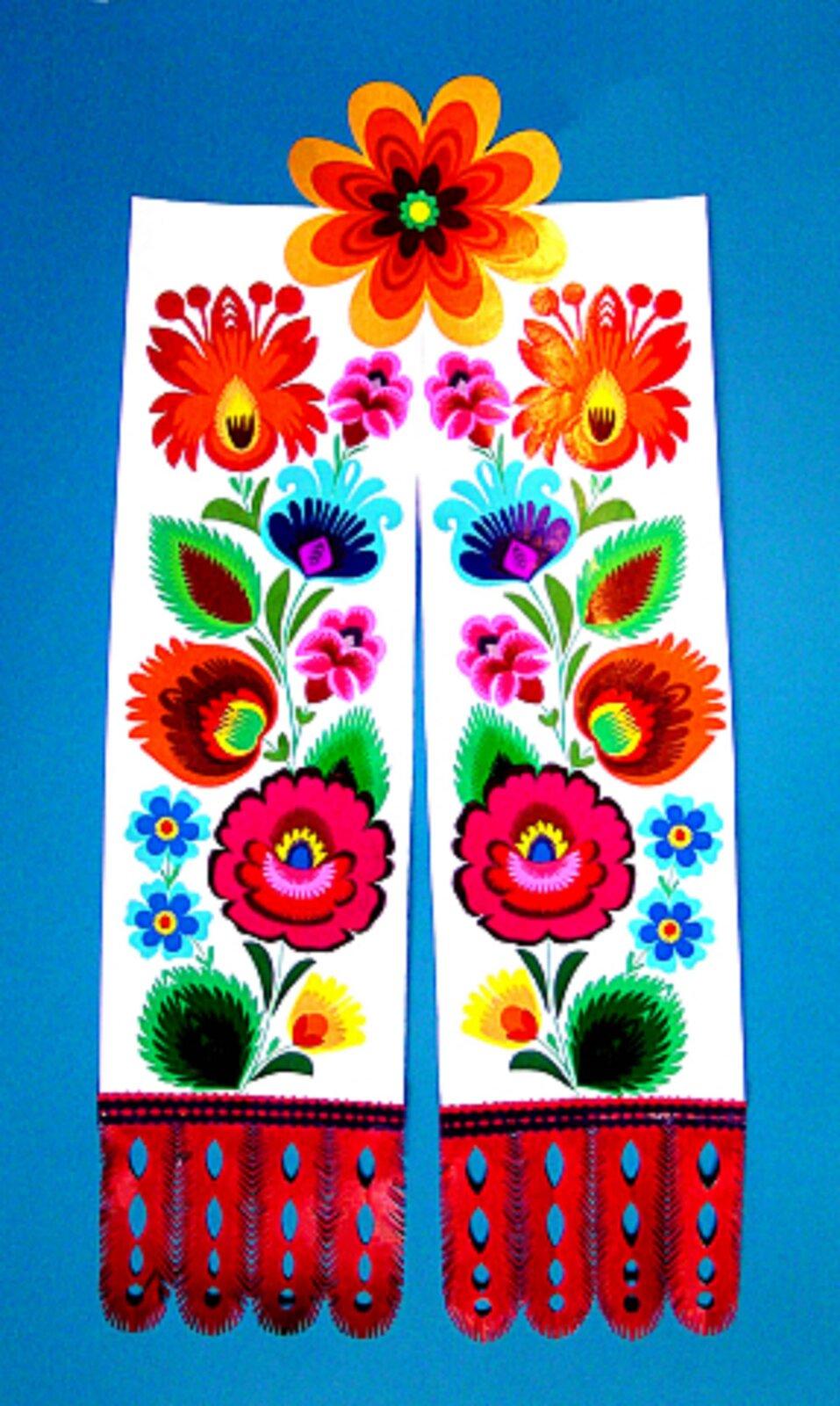 Ilustracja przedstawia łowicką tasiemkę. Są to dwie takie same części, zakończone są czerwonymi wypustkami. Na obu znajdują się kwiaty wróżnych kolorach oraz zielone listki. Wzór ułożony jest pionowo. Dwie taśmy łączy znajdujący się pośrodku górnej części kwiat.