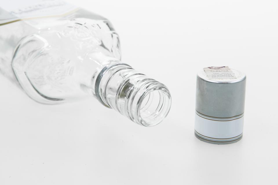 Drugie zdjęcie przedstawia leżącą szklaną butelkę skierowaną otworem wkierunku prawego rogu zdjęcia. Naprzeciw szara długa nakrętka butelki.