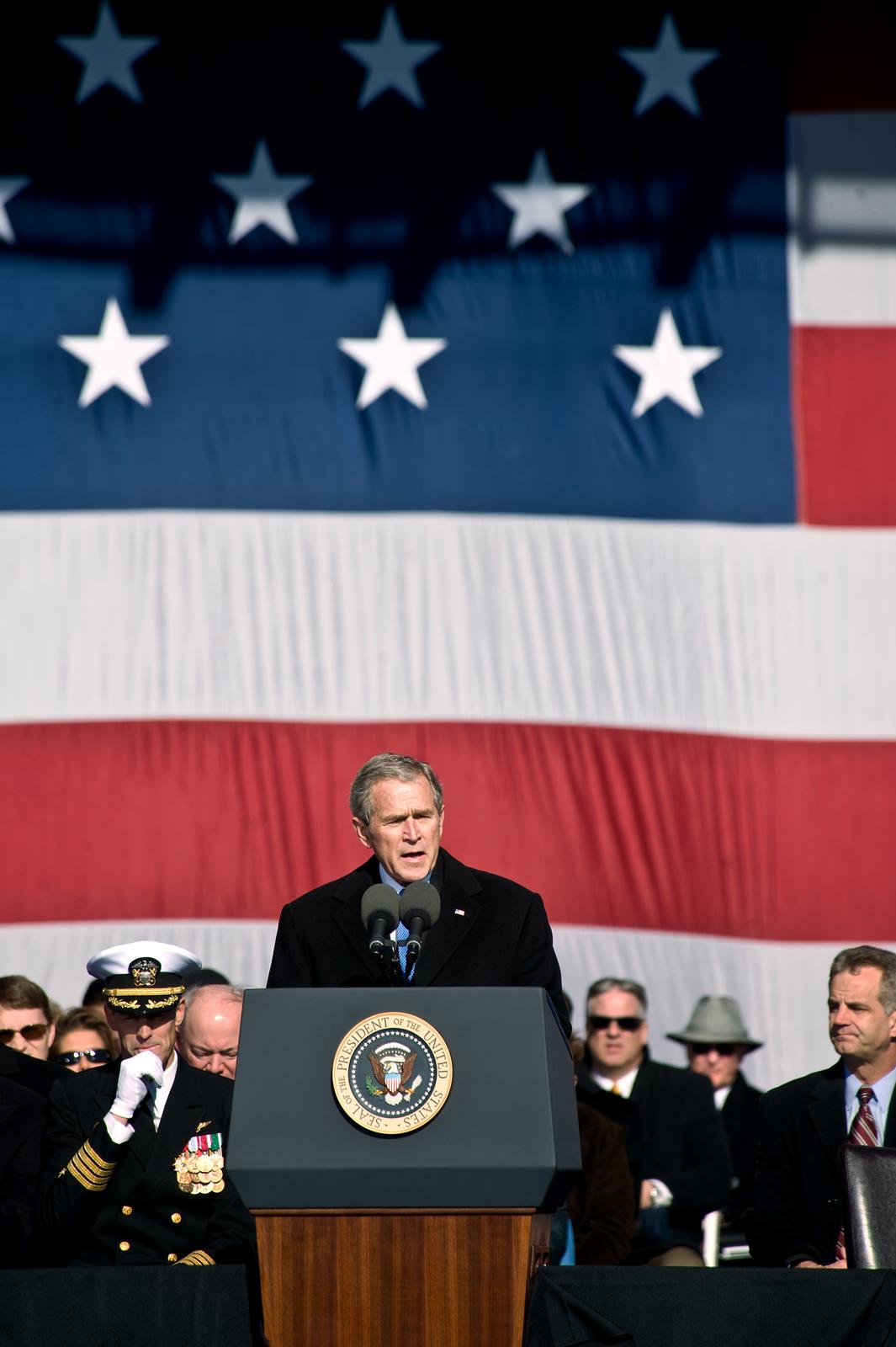 Zdjęcie przedstawia George`a Busha wtrakcie przemówienia. Prezydent Bush stoi za mównicą. Ubrany wczarny płaszcz wygłasza przemówienie. Wtle siedzą politycy, wojskowi. Wszyscy ubrani na czarno. Niektóre osoby mają czarne okulary. Na ścianie, wgłębi zdjęcia, rozwieszona duża flaga amerykańska. Biało czerwone poziome pasy. Powyżej niebieski prostokąt zbiałymi pięcioramiennymi gwiazdami.